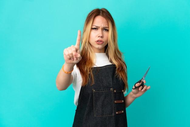 Jong kappersmeisje over geïsoleerde blauwe achtergrond die één met ernstige uitdrukking telt