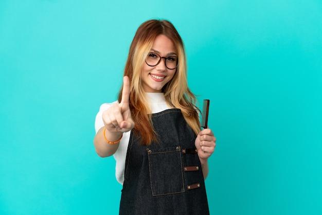 Jong kappersmeisje over geïsoleerde blauwe achtergrond die een vinger toont en opheft