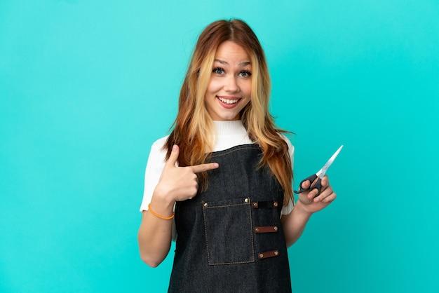 Jong kappersmeisje over geïsoleerde blauwe achtergrond met verrassingsgelaatsuitdrukking