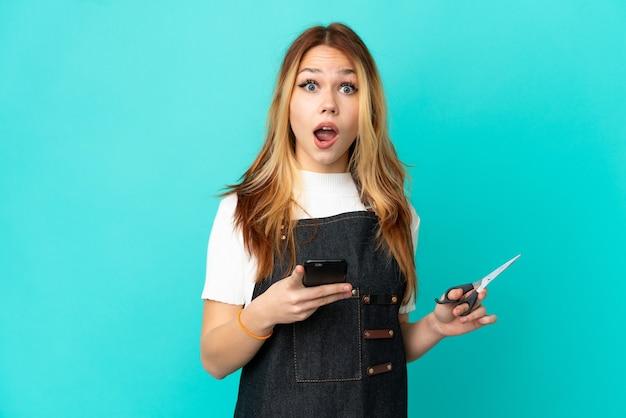 Jong kappersmeisje over geïsoleerde blauwe achtergrond verrast en verzendt een bericht