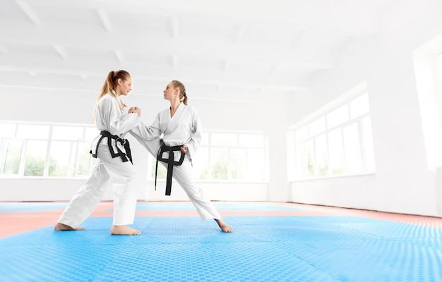 Jong karatemeisje die aan haar partner uitrekkende been helpen alvorens op te leiden.