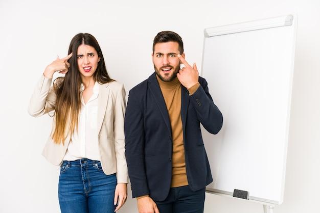 Jong kaukasisch bedrijfspaar dat een teleurstellinggebaar met wijsvinger toont.