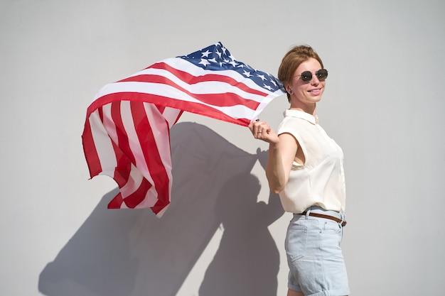 Jong kaukasisch glimlachend meisje die in zonnebril de vlag van de vs erachter houden als een mantel die door wind wordt gegolfd