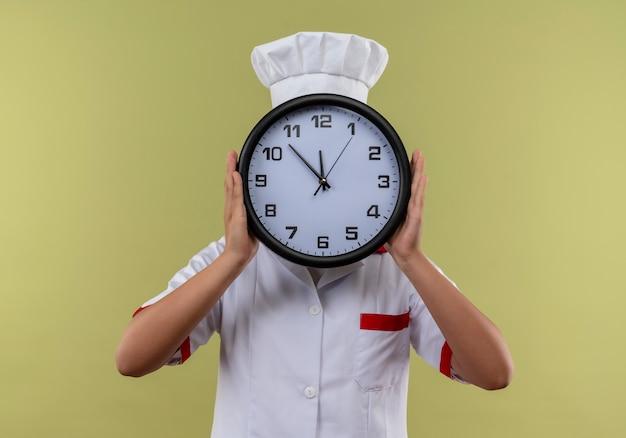 Jong kaukasisch kokmeisje in eenvormige chef-kok sluit gezicht met klok die op groene achtergrond met exemplaarruimte wordt geïsoleerd