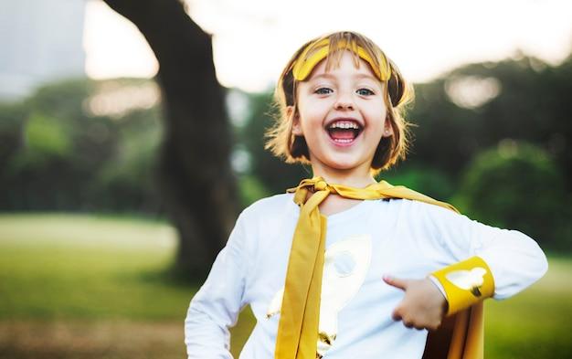 Jong kaukasisch meisje dat dragend superherokostuum in het park glimlacht