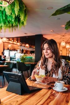Jong kaukasisch meisje dat een gezond ontbijt voor haar dieet in een restaurant heeft.