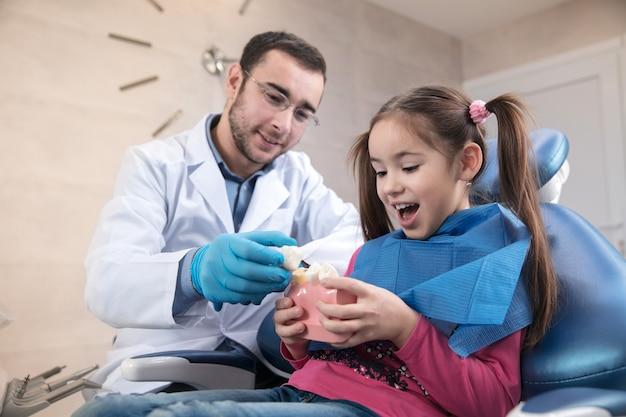 Jong kaukasisch meisje dat het kantoor van de tandarts bezoekt