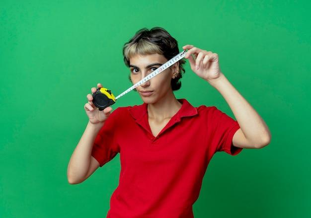 Jong kaukasisch meisje dat met de bandmeter van de pixiekapselholding camera bekijkt die op groene achtergrond met exemplaarruimte wordt geïsoleerd