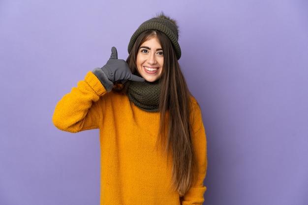 Jong kaukasisch meisje dat met de winterhoed op purpere muur wordt geïsoleerd die telefoongebaar maakt. bel me terug teken