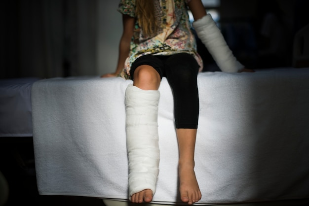 Jong kaukasisch meisje met gebroken been in gegoten gips
