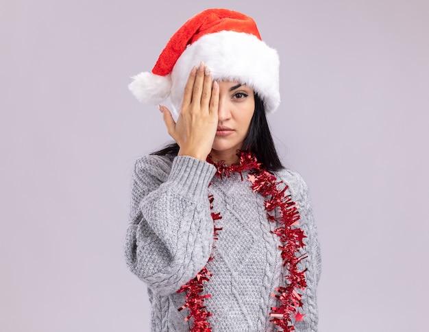 Jong kaukasisch meisje met kerstmuts en klatergoud slinger om nek kijken camera die de helft van het gezicht bedekt met hand geïsoleerd op een witte achtergrond met kopie ruimte