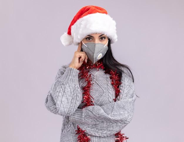 Jong kaukasisch meisje met kerstmuts en klatergoud slinger rond nek met beschermend masker kijken camera doen denk gebaar geïsoleerd op een witte achtergrond met kopie ruimte