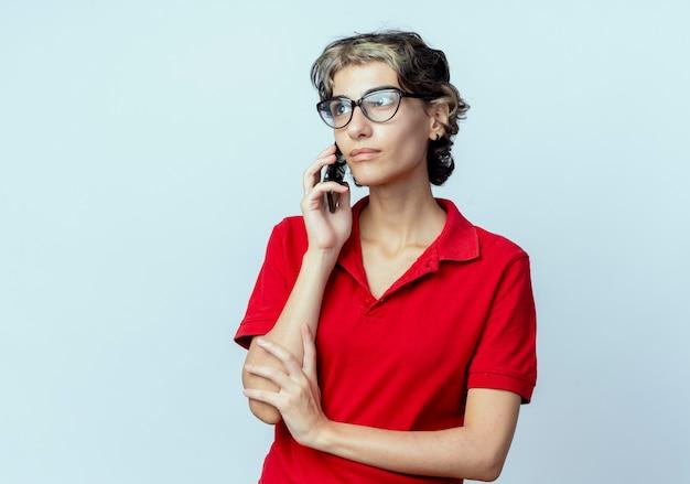 Jong kaukasisch meisje met pixie-kapsel met een bril die aan de telefoon praat en er recht uitziet en de hand op de arm legt