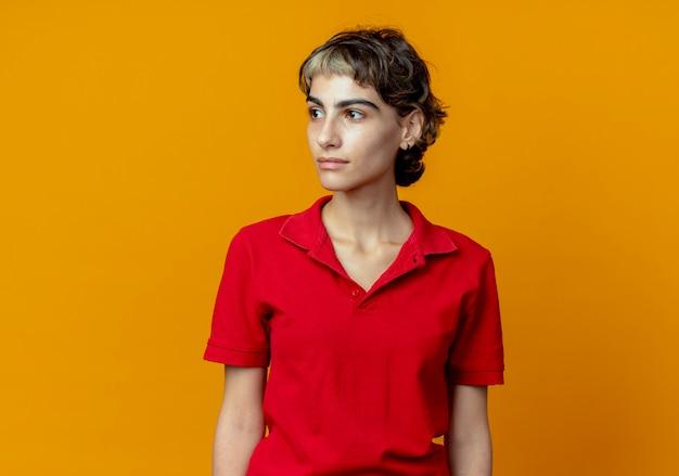 Jong kaukasisch meisje met pixiekapsel die kant bekijken die op oranje achtergrond met exemplaarruimte wordt geïsoleerd
