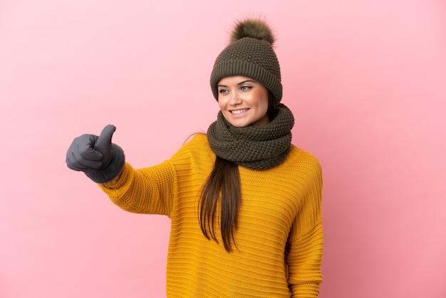 Jong kaukasisch meisje met wintermuts geïsoleerd geven een duim omhoog gebaar