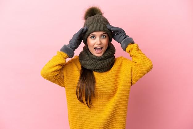 Jong kaukasisch meisje met wintermuts geïsoleerd met verrassingsuitdrukking