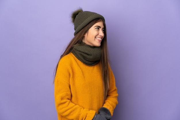 Jong kaukasisch meisje met wintermuts geïsoleerd op paarse achtergrond op zoek naar de kant en glimlachend