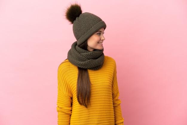 Jong kaukasisch meisje met wintermuts geïsoleerd op zoek kant