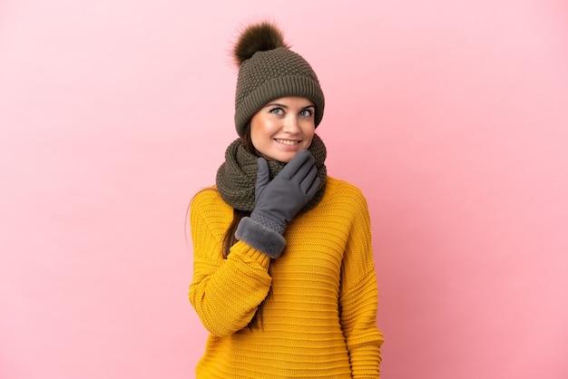 Jong kaukasisch meisje met wintermuts geïsoleerd opkijkend terwijl ze lacht