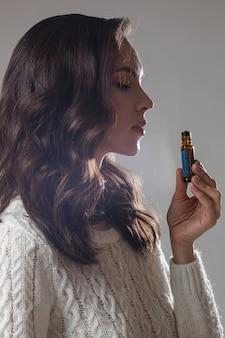 Jong kaukasisch model met lang donker haar poseert voor de camera met de hand in de buurt van haar gezicht