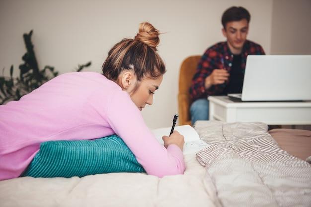 Jong kaukasisch paar dat en laptop ontspant tijdens het lezen van iets en op bed ligt