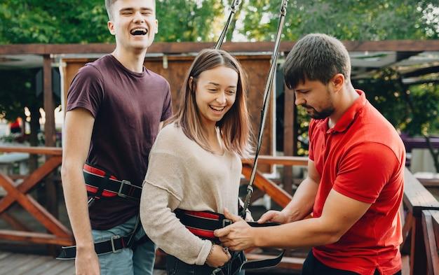 Jong kaukasisch paar dat op zoek is naar nieuwe gevoelens die klaar zijn om op een kabelbaan af te dalen, lacht en wacht erop