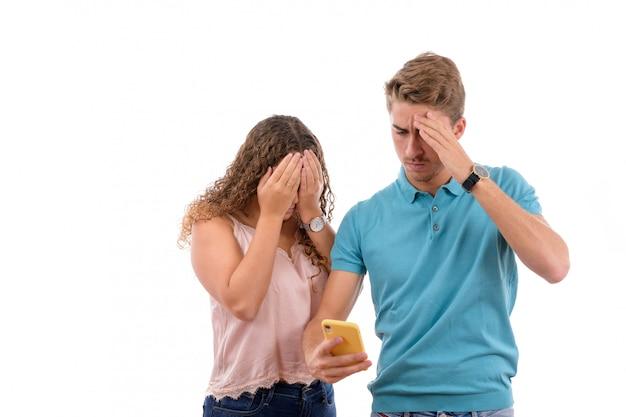 Jong kaukasisch paar dat slecht nieuws op hun mobiele telefoon ontvangt die op witte achtergrond wordt geïsoleerd