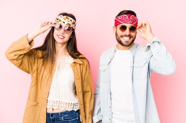 Jong kaukasisch paar die de kleren van een muziekfestival dragen geïsoleerd opgewonden houden ok gebaar op oog.