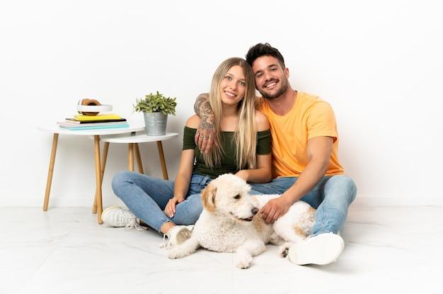 Jong kaukasisch paar met hond die thuis knuffelen blijft