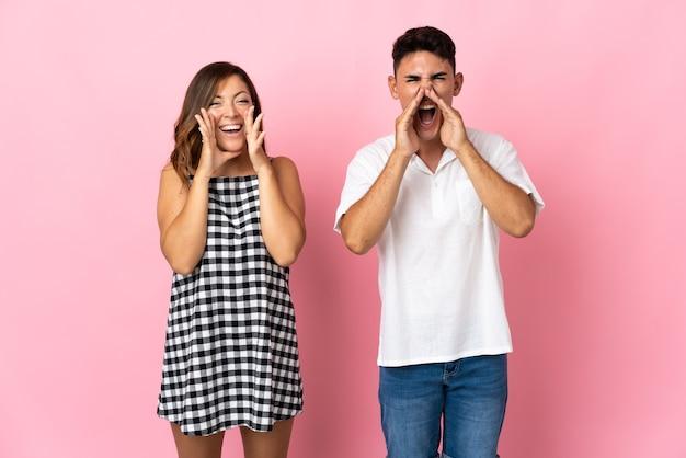 Jong kaukasisch paar op roze die met wijd open mond schreeuwen