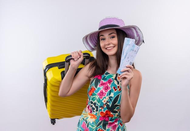 Jong kaukasisch reizigersmeisje die sutcase en kaartjes van de hoedenholding op geïsoleerde witte achtergrond dragen