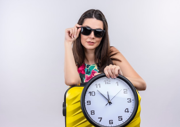 Jong kaukasisch reizigersmeisje die zonnebril dragen die klok op geïsoleerde witte achtergrond houden