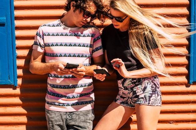 Jong kaukasisch stel gebruikt moderne mobiele telefoons
