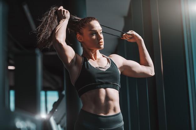 Jong kaukasisch sterk spier vrouwelijk bodybuilder bindend haar terwijl status in gymnastiek naast venster. als je het beu bent om opnieuw te beginnen, stop dan met opgeven.