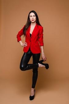 Jong kaukasisch vrouwelijk model met lang donker recht haar in rood jasje, zwarte leren broek en zwarte schoenen