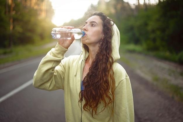 Jong kaukasisch vrouwen drinkwater na het runnen van asfaltweg