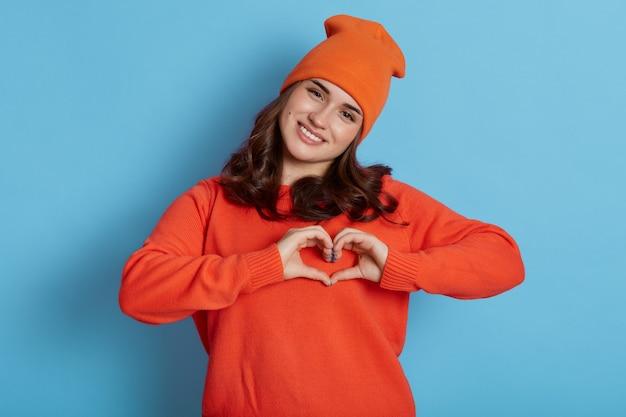 Jong kaukasisch wijfje dat oranje sweater en hoed draagt die hartgebaar met handen maakt en direct camera met gelukkige uitdrukking bekijkt, die over blauwe muur wordt geïsoleerd.