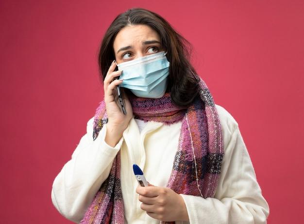 Jong kaukasisch ziek meisje dat een gewaad en een sjaal met een masker draagt die over de thermometer van de telefoonholding spreekt die kant bekijkt die op karmozijnrode achtergrond wordt geïsoleerd