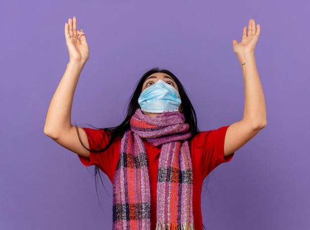 Jong kaukasisch ziek meisje dat masker en sjaal draagt die thermometer omhoog kijkt en handen opheft biddende en zegenende god die op purpere muur wordt geïsoleerd