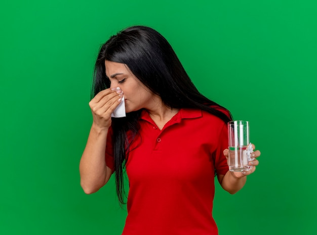 Jong kaukasisch ziek meisje houdt pak tabletten glas water en neus afvegen met servet met gesloten ogen geïsoleerd op groene achtergrond met kopie ruimte