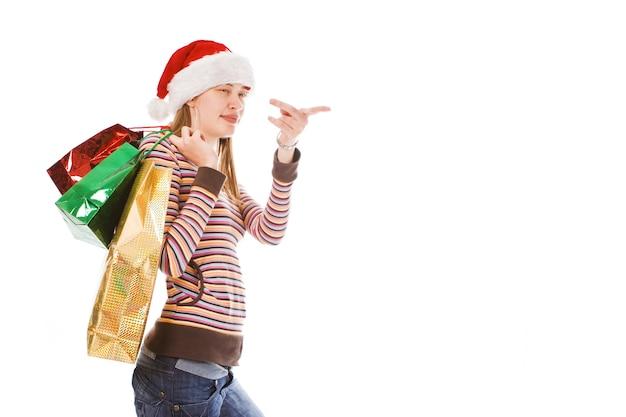 Jong kerstmeisje in rode hoed met pakket laat vinger zien