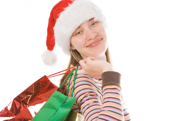 Jong kerstmismeisje in rode hoed met pakket over witte achtergrond