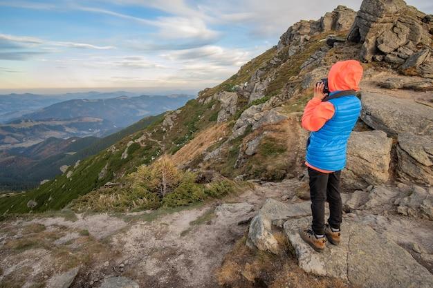 Jong kind jongen wandelaar fotograferen in de bergen genieten van uitzicht op verbazingwekkende berglandschap.