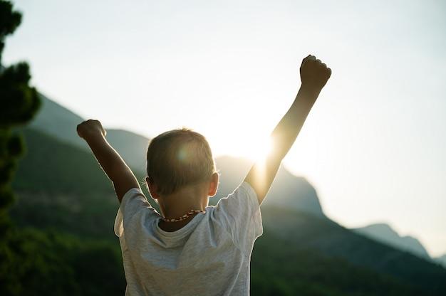 Jong kind met armen in de lucht die met opkomende zon instemt
