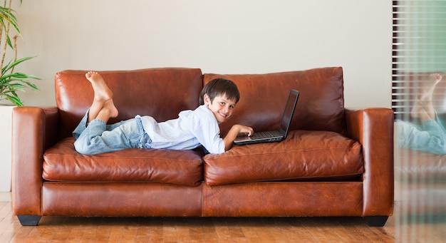 Jong kind met een laptop op de bank