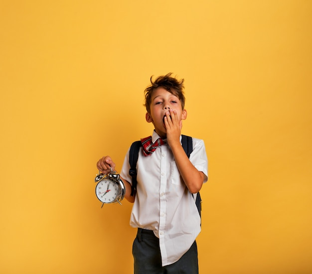Jong kind student met rinkelende wekker is lui naar school gaan. gele achtergrond.