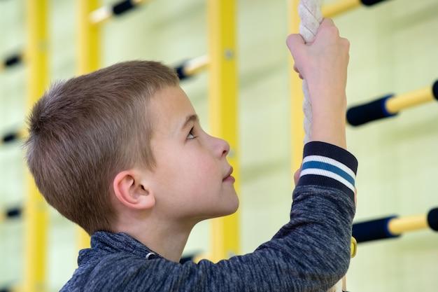 Jong kindjongen die op een bar van de muurladder uitoefenen binnen de ruimte van de sportengymnastiek in een school.