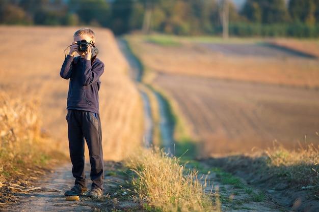 Jong kindjongen met fotocamera die beeld van tarwegebied nemen