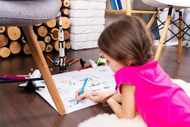 Jong kindmeisje vrouwelijk het schilderen astronautenkostuum door kleurrijke pennen en het dromen over kosmos met speelgoed van de kosmonautconstructeur