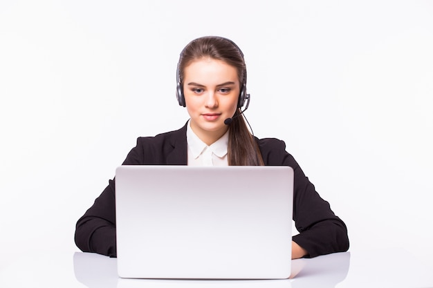 Jong klantenservicemeisje met een hoofdtelefoon op haar werkplaats dat op witte muur wordt geïsoleerd